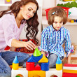 Family with child playing bricks. — Stock Photo
