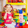 Stock Photo: Child with puzzle, block and construction set in play room.