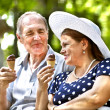 Happy old couple with ice-cream. — Stock Photo