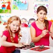 Stock Photo: Teacher and kid playing with clay.