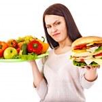 kadın meyve ve hamburger arasında seçim yapma — Stok fotoğraf