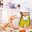 Stock Photo: Child knead dough at kitchen.