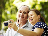 Happy old couple with camera — Stock Photo