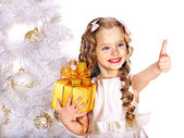 Child with gift box near white Christmas tree. — Stok fotoğraf