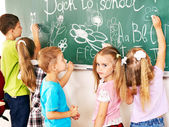 Children writing on blackboard. — Stock Photo
