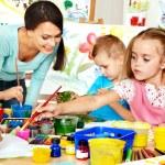 Children with teacher painting. — Stock Photo