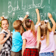 Children writing on blackboard. — Stockfoto