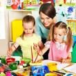 Children with teacher painting. — Stock Photo