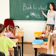 Teacher writting at blackboard in classroom — Stock Photo