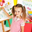 Stock Photo: Child painting at easel.