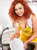 Woman washing dishes at kitchen. — Stockfoto