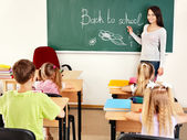 Teacher writting at blackboard in classroom — Stockfoto