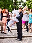 Bräutigam trägt seine braut über die schulter. — Stockfoto
