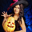 Stock Photo: Witch holding pumpkin