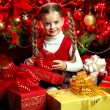 Stock Photo: Child with gift box near Christmas tree.