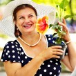 Happy senior woman with flower. — Stock Photo