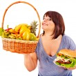 Woman choosing between fruit and hamburger. — Stock Photo #31639601