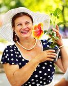 Feliz mulher sênior com flor. — Fotografia Stock