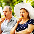 Happy old couple with ice-cream. — Stock Photo #32111715