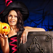 Stock Photo: Witch woman holding old book and pumpkin