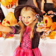Girl in carnival costume on Halloween holding cakes — Stock Photo #32111887