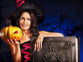 Witch woman holding old book and pumpkin — Stockfoto