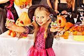 Girl in carnival costume on Halloween holding cakes — Stock Photo