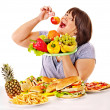Woman choosing between fruit and hamburger. — Stock Photo #32533801