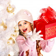 Child in hat and mittens holding red gift box near white Christmas tree. — Stock Photo