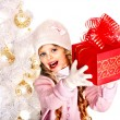 Child in hat and mittens holding red gift box near white Christmas tree. — Stock Photo #32946369