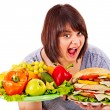 Stock Photo: Woman choosing between fruit and hamburger.