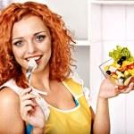 Woman eating salad at kitchen. — Stock Photo