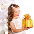Child with gift box near white Christmas tree. — Stock Photo