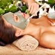 Woman having clay facial mask apply by beautician. — Stock Photo