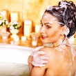 Stock Photo: Womwashing hair in bubble bath.