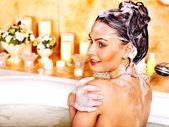 Woman washing hair in bubble bath. — Stock Photo