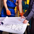 Business people and man in builder uniform — Stock Photo