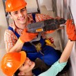 Stock Photo: Family in builder uniform indoor.