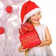 Child in Santa hat with gift box near white Christmas tree. — Stock Photo #35335079