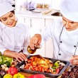 Man and woman in chef hat cooking chicken — Stock Photo