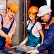 Group people builder cutting ceramic tile. — Stock Photo
