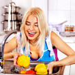 Woman washing fruit at kitchen. — Stock Photo