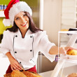 Female chef in Santa hat  holding  food. — Stock Photo