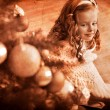 Little girl  receiving gifts under Christmas tree. — Stock Photo