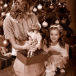 Kid with mother receiving gifts under Christmas tree. — Photo