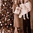 Stock Photo: Family with children dressing Christmas tree.