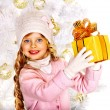Child in hat and mittens holding Christmas gift box. — Foto de Stock