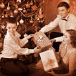 Family with children  receiving gifts under Christmas tree. — Foto de Stock