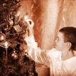Stock Photo: Child ignites candles on Christmas tree.