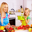 Stock Photo: Mother and daughter at kitchen.